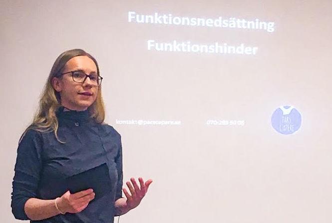 """Aline står och håller en föreläsning. I bakgrunden ser man presentationen med orden """"funktionsnedsättning"""" och """"funktionsvariation"""""""