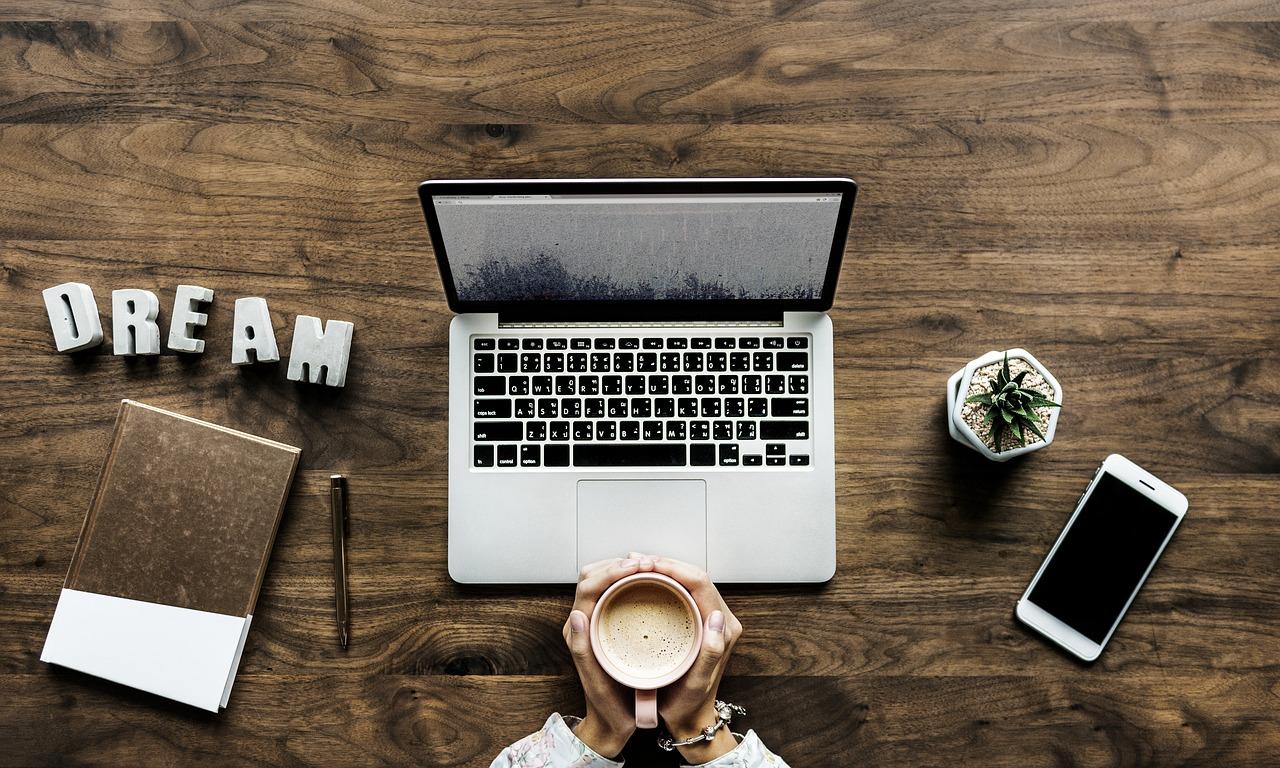 """Ett skrivbord med en dator, två händer som omsluter en kopp kaffe, bokstäverna """"DREAM"""", en anteckningsbok, en penna, en kaktus och en mobil."""